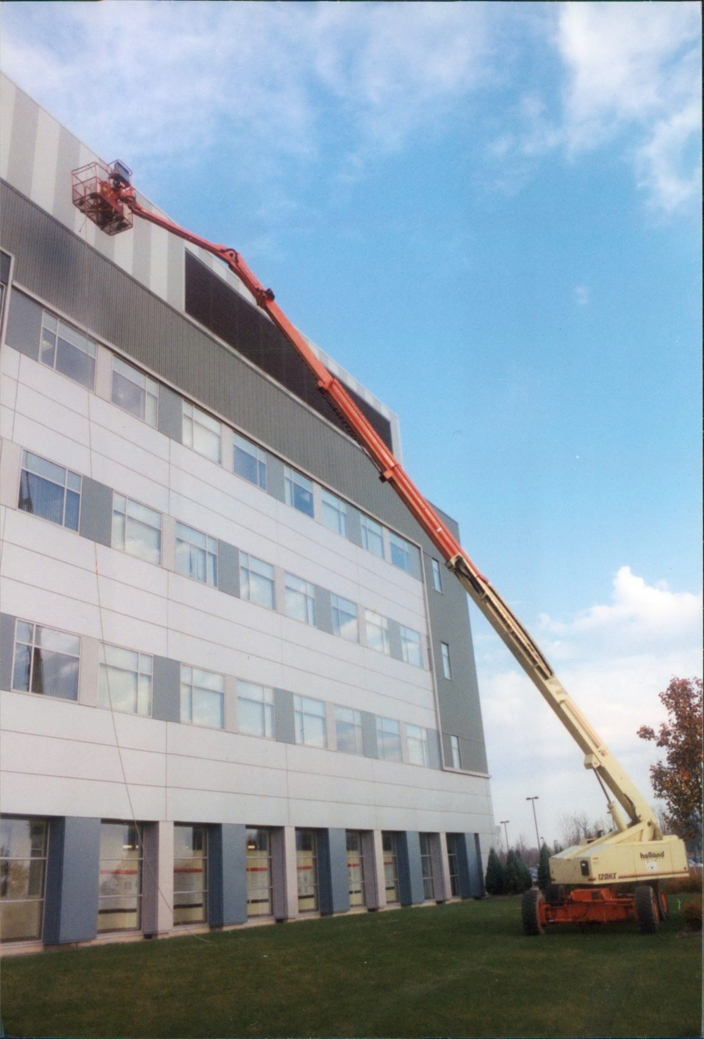 Cleaning aluminum siding on building using 120 foot man lift